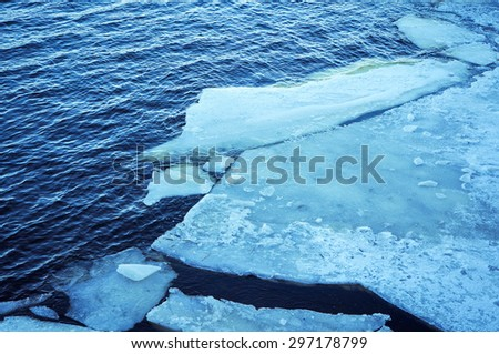 large pieces of crackled ice on blue river waters in winter - stock photo