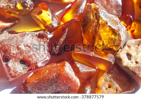 Large pieces of transparent and opaque broken natural amber stones on white background - stock photo