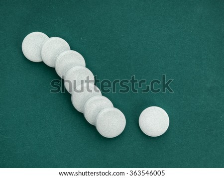 Large pills lined up. Vitamin background on green blue.