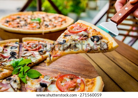 Large pizza on a wooden table. Restaurant - stock photo