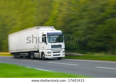 Large plain white truck with motion blur (in camera effect) - stock photo