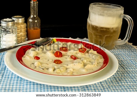 Large plate of crab chowder filled with oyster and shrimp and garnished with sliced tomato.  Served with cold beer in frosted mug. - stock photo