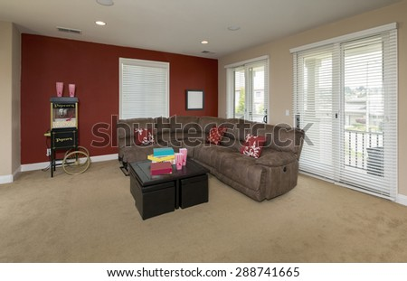 Large play room with TV, sport and games and red wall. Family room with pool table, sofa and tv. - stock photo