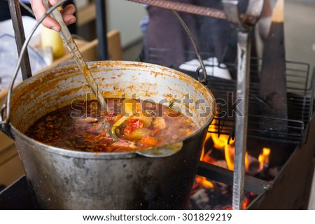 Large pot of meat and vegetable stew simmering over an open fire suspended over the flames from an iron frame - stock photo