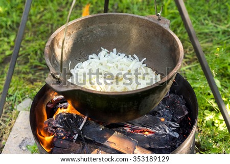 Large pot over a campfire cooking in cast-iron cauldron in nature. Food, Camping, cooking onion over a fire in the boiler - stock photo