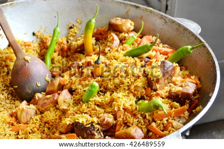 Large pot with Uzbek pilaf with tomatoes and green chilli peppers - stock photo