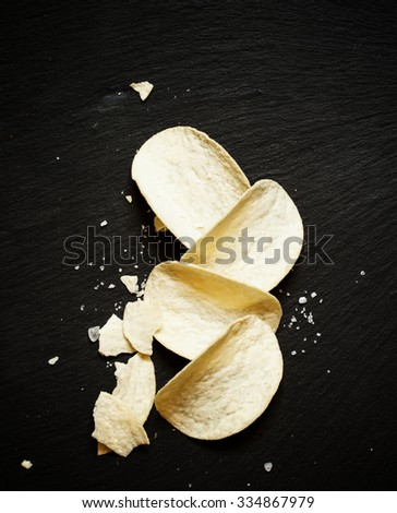 Large potato chips with sea salt on dark stone background, top view - stock photo