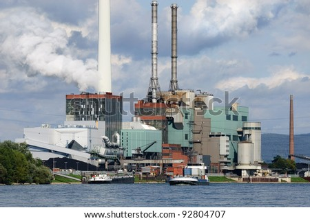 Large power plant blowing out steam beside a blue river - stock photo