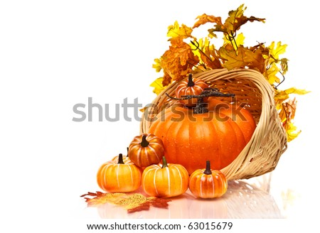 Large pumpkin and small pumpkins in a a wicker basket on a white background - stock photo