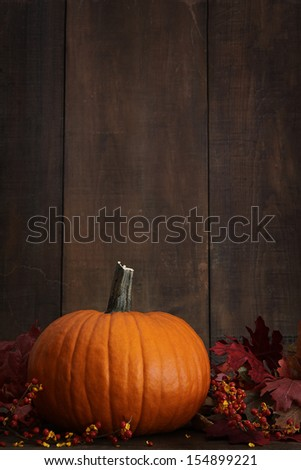 Large pumpkin with leaves against a wood background - stock photo