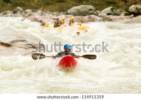 LARGE RAFTING BOAT CHASING A KAYAK ON PASTAZA RIVER, ECUADOR  - stock photo