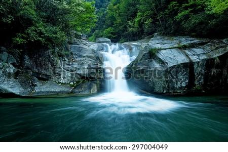 Large rain forest waterfall, sun beams, and mossy rocks - stock photo