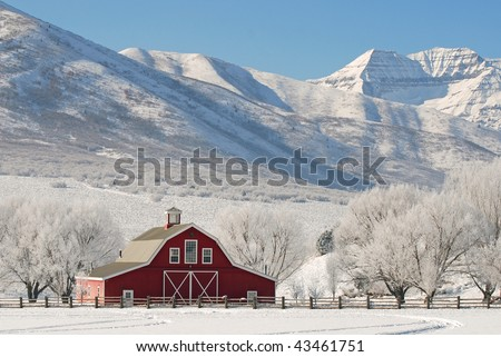 Large red barn in winter snow with tall mountains in the background. - stock photo