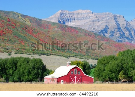Large red barn with Timpanogos Mountain and the Wasatch mountain range in the background with autumn colors. - stock photo
