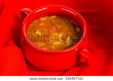 Large red bowl full of chicken taco soup against red background. - stock photo