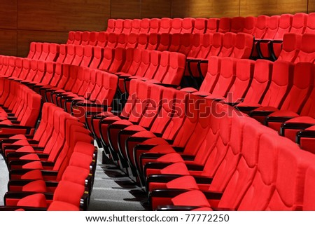 Large red recliners stand rows in an empty hall - stock photo