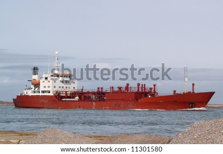 Large red ship steaming through a narrow channel