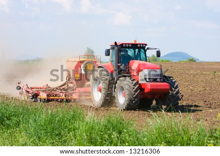 Large red tractor working in the field. Blue sky, brown soil - stock photo