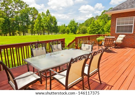 Large residential wooden backyard deck with furniture