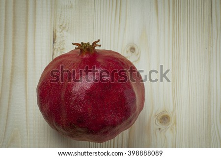 large ripe red pomegranate on a wooden background - stock photo
