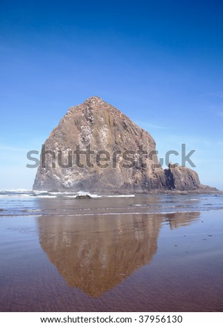 Large rock at ocean beach on sunny day, with reflection in the wet sand - taken at historic Haystack Rock at Cannon Beach, Oregon.