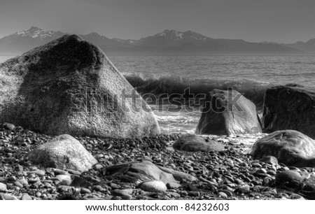 Large rocks and waves at Diamond Beach on the coast of Alaska in black and white.