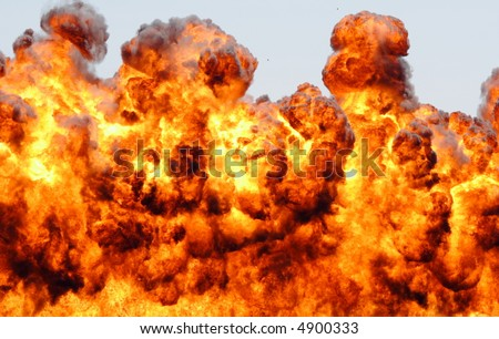 Large rolling explosion throwing fire into the sky - stock photo