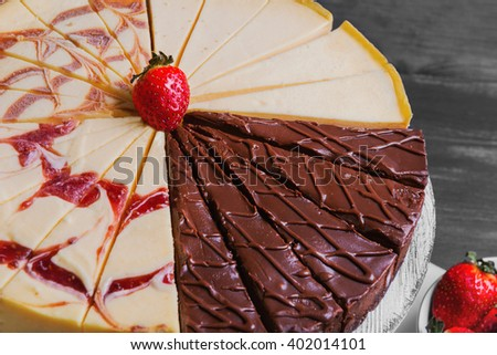 Large round assorted cheesecake, raspberry, caramel, chocolate, caramel, cut into pieces on a white pedestal, white plate with strawberry on a black wooden background - stock photo