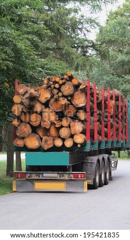 large round wooden beams loaded on semi truck - stock photo