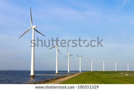 Large row of windmills on the shore