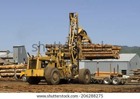Large rubber tire log handler or loader removes a loads of cedar logs from a logging truck at a Oregon specialty wood product mill - stock photo