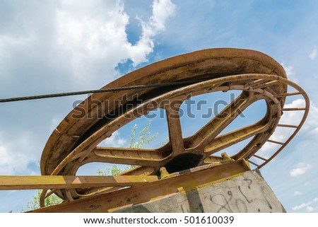 large rusty wheel rope pulley against blue sky and white cloud