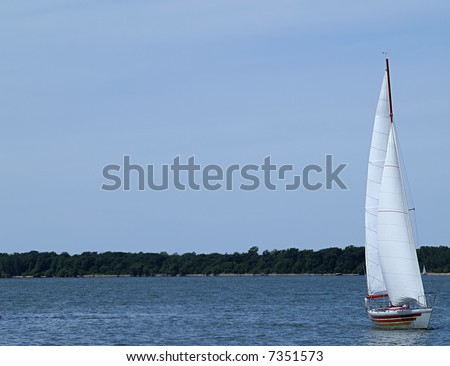 Large sail boat floats along on the slightly choppy surface of the lake