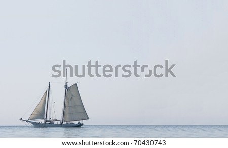 large sailing boat with guests aboard in Charleston Harbor on a clear blue day - stock photo