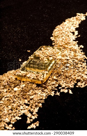large samples of pure gold in various forms including coins, ingots, bars, dust and nuggets - stock photo