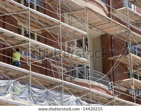Large scaffolding at a construction site with non-recognizable worker. - stock photo