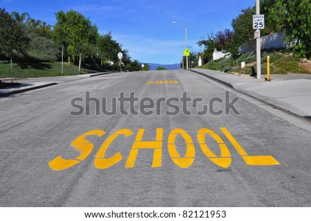 "Large ""SCHOOL"" sign painted on an urban street - stock photo"