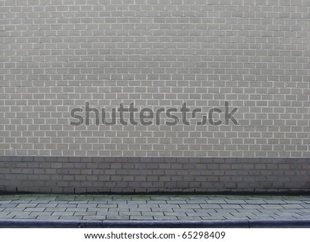 large section of a gray brick wall with sidewalk