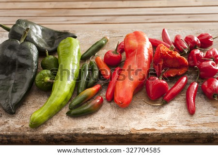 Large selection of fresh chili peppers of different varieties and colors displayed on a wooden kitchen counter, used as a pungent spice in cooking - stock photo