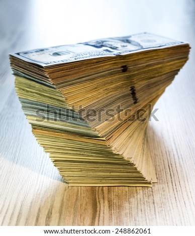 Large shaped stack of US cash. The stack of US cash in mixed notes of different colors and tones, positioned on the wooden table - stock photo