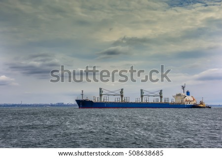 large ship cargo ship with cranes in the sea followed by a tug to the shore. In the background visible city building. Beautiful sky with clouds. Overcast