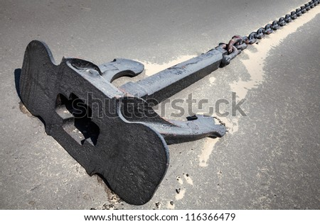 Large ship's mooring anchor with chain on dry ground in the port - stock photo