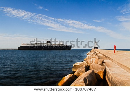 Large ship, the SS Badger car ferry coal-fired steamer, leaves port and passes by the North Breakwater Light in Ludington, Michigan. - stock photo