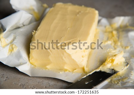 Large Softened Stick of Butter on Wrapping Ready to Eat - stock photo