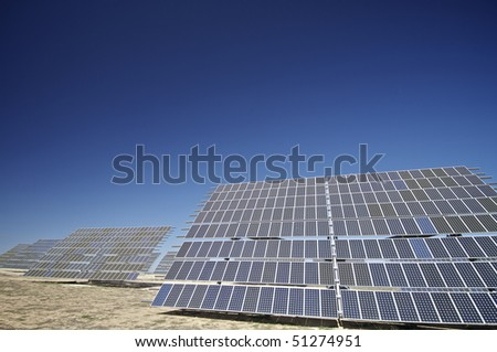 large solar panels with clear blue sky - stock photo