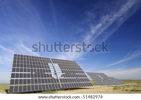large solar panels with cloudy blue sky - stock photo