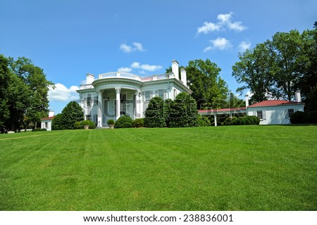 Large Southern Mansion with Beautiful Lawn and Trees - stock photo