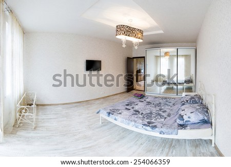 Large spacious bedroom with double bed. Panorama of the interior of a hotel room. Interior light room in a modern style. - stock photo
