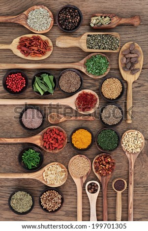 Large spice and herb selection in wooden bowls, spoons and scoops over oak wood background. - stock photo