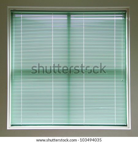 Large square window covered with green blinds. - stock photo